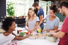 Группа в составе друзья варя завтрак в кухне совместно стоковые изображения rf