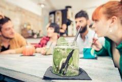 Группа в составе друзья выпивая коктеиль в пабе Стоковая Фотография