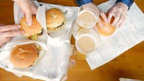 Группа в составе друзья выпивая пиво и есть закуски на деревянной предпосылке, руки с бургерами акции видеоматериалы