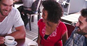 Группа в составе друзья в кофейне смотря таблетку цифров акции видеоматериалы