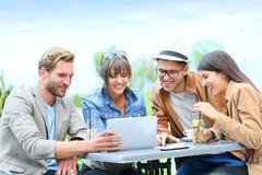 Группа в составе друзья в ресторане используя таблетку Стоковая Фотография