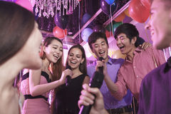 Группа в составе друзья держа микрофоны в ночном клубе и поя совместно караоке Стоковое фото RF