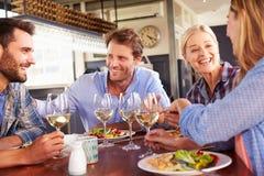 Группа в составе друзья есть на ресторане Стоковое фото RF
