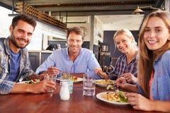 Группа в составе друзья есть на ресторане Стоковые Фото