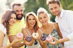 Группа в составе друзья есть donuts outdoors Стоковое фото RF