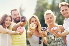 Группа в составе друзья есть donuts outdoors Стоковое Изображение