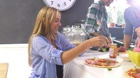 Группа в составе друзья делая пиццу в кухне совместно видеоматериал