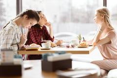 Группа в составе друзья изучает совместно в кафе Стоковое фото RF