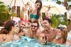 Группа в составе друзья имея партию в бассейне выпивая Шампань Стоковое Изображение RF