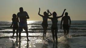 Группа в составе друзья имея партию в океане и бег к пляжу на заходе солнца в замедленном движении видеоматериал