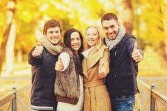 Группа в составе друзья имея потеху в парке осени стоковое изображение