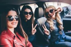 Группа в составе друзья имея потеху на автомобиле Петь и смеяться над в городе Стоковые Фотографии RF