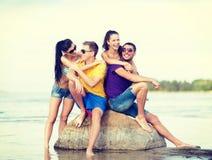 Группа в составе друзья имея потеху на пляже Стоковая Фотография