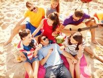 Группа в составе друзья имея потеху на пляже Стоковые Фото