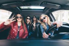 Группа в составе друзья имея потеху разжигает привод автомобиль Петь и смеяться над на дороге Стоковая Фотография RF