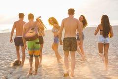 Группа в составе друзья идя на пляж на заходе солнца Стоковые Изображения