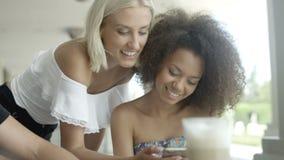 Группа в составе друзья наблюдая фото на телефоне и смеяться над сток-видео