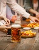 Группа в составе друзья наслаждаясь вечерними напитками с пивом Стоковые Изображения