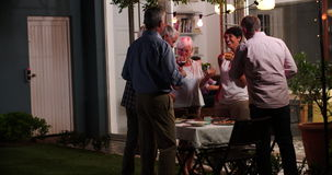 Группа в составе друзья наслаждаясь внешней партией вечерних напитков сток-видео