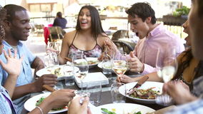 Группа в составе друзья наслаждаясь едой на внешнем ресторане акции видеоматериалы