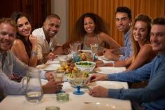 Группа в составе друзья наслаждаясь официальныйом обед дома совместно стоковые фотографии rf