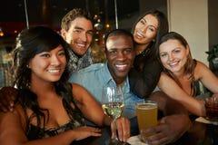 Группа в составе друзья наслаждаясь питьем на баре совместно Стоковые Изображения RF