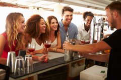 Группа в составе друзья наслаждаясь питьем на открытом баре Стоковая Фотография RF