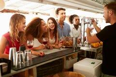 Группа в составе друзья наслаждаясь питьем на открытом баре Стоковые Фотографии RF