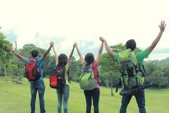 Группа в составе друзья на пешем повышении их рука совместно стоковые фотографии rf
