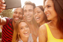 Группа в составе друзья на празднике принимая Selfie с мобильным телефоном