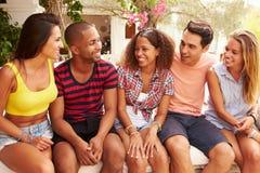 Группа в составе друзья ослабляя Outdoors на празднике совместно стоковое фото rf