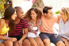 Группа в составе друзья ослабляя Outdoors на празднике совместно стоковые изображения rf