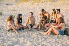 Группа в составе друзья поя на пляже на заходе солнца Стоковое фото RF
