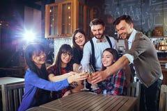 Группа в составе друзья празднует имеющ потеху беседуя с glasse Стоковые Фотографии RF