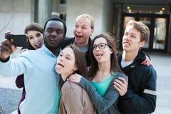 Группа в составе друзья принимая чокнутое Selfie Стоковая Фотография