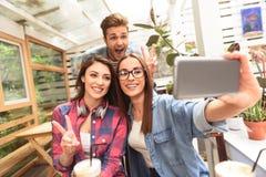 Группа в составе друзья принимая Selfie стоковое изображение rf