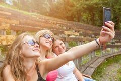 Группа в составе друзья принимая selfie outdoors Стоковая Фотография