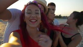 Группа в составе друзья принимая selfies на пляж на заходе солнца сток-видео