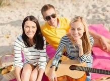 Группа в составе друзья при гитара имея потеху на пляже Стоковое Фото