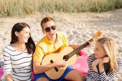 Группа в составе друзья при гитара имея потеху на пляже Стоковое фото RF