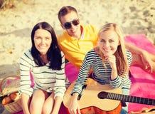 Группа в составе друзья при гитара имея потеху на пляже Стоковая Фотография RF