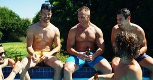 Группа в составе друзья сидя на стороне бассейна и наслаждаясь пить видеоматериал