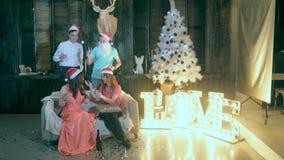 Группа в составе друзья танцуя около рождественской елки отпразднуйте носить santa мати шлемов дочи рождества торжества акции видеоматериалы