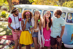 Группа в составе друзья дуя пузыри от палочки пузыря в парке Стоковое фото RF