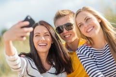 Группа в составе друзья фотографируя с smartphone Стоковое фото RF