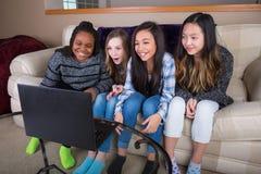Группа в составе 4 друз смотря текл тв-шоу на compu компьтер-книжки Стоковая Фотография RF