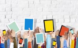 Группа в составе руки держа приборы цифров на кирпичной стене стоковые изображения