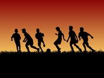 Группа в составе силуэта ребенк футбола Стоковые Изображения