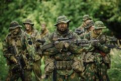 Группа в составе силы специального назначения солдат во время рейда в лесе стоковое изображение rf