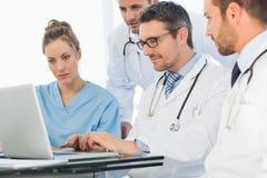 Группа в составе сконцентрированные доктора используя компьтер-книжку Стоковые Фото